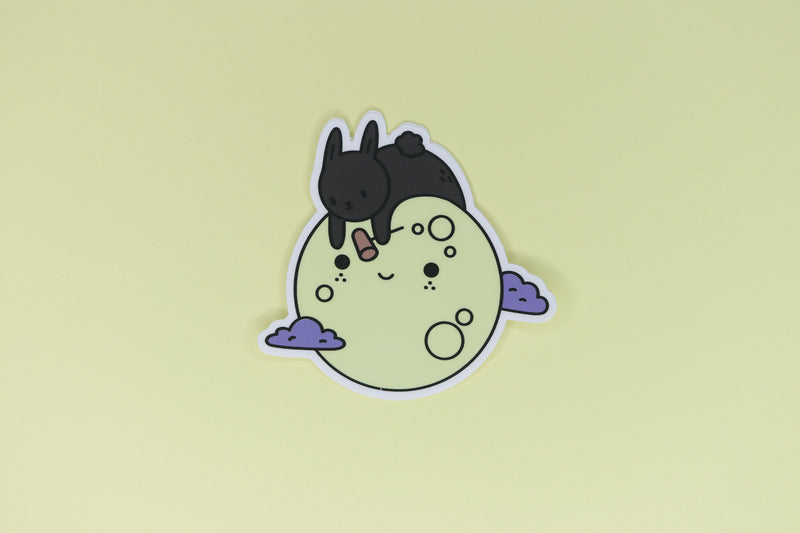 sticker of black rabbit on yellow moon with purple clouds