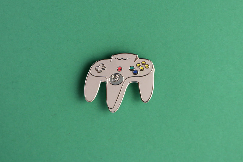 Grey N64 Controller Hard Enamel Pin on a Green Paper Background