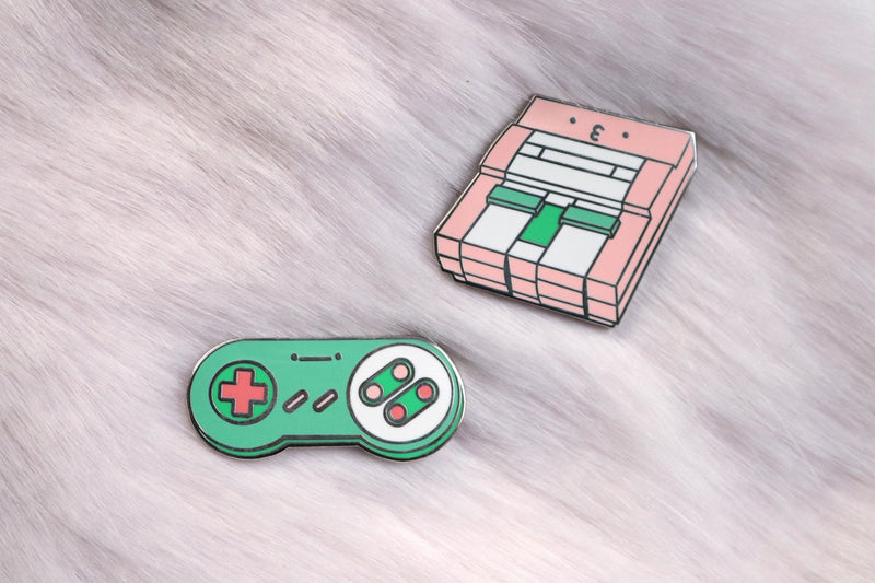 Pink SNES Consoles and Green SNES Controller Pins on Pink Fur Background