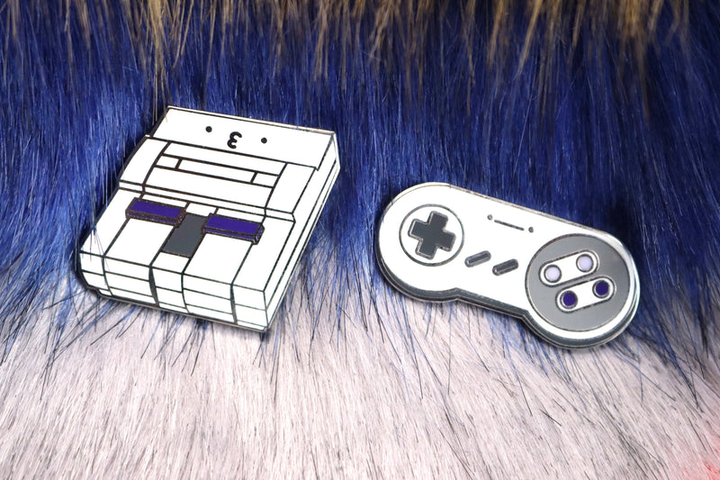 SNES Console and Controller Hard Enamel Pins on Blue and Pink Fur Background