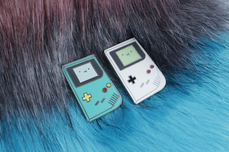 Teal and Gray Game Boy Hard Enamel Pins on Gray and Blue Fur Background