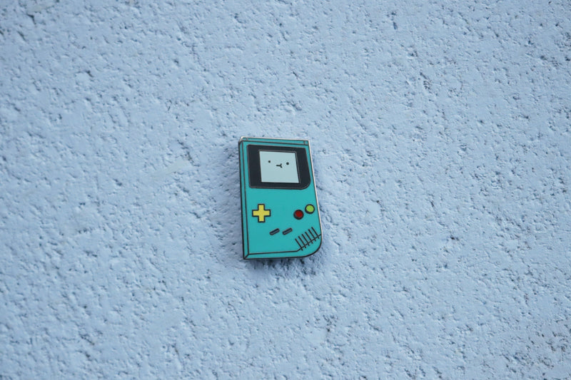 Teal Game Boy Color on Blue Cork Background