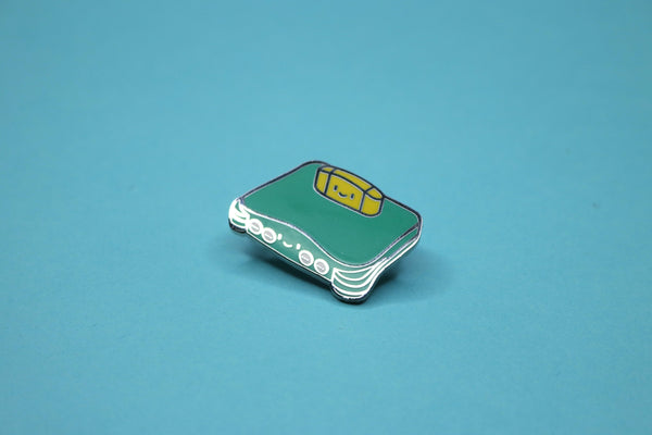 Jungle Green N64 with Yellow Game Cartridge Enamel Pin on Teal Background