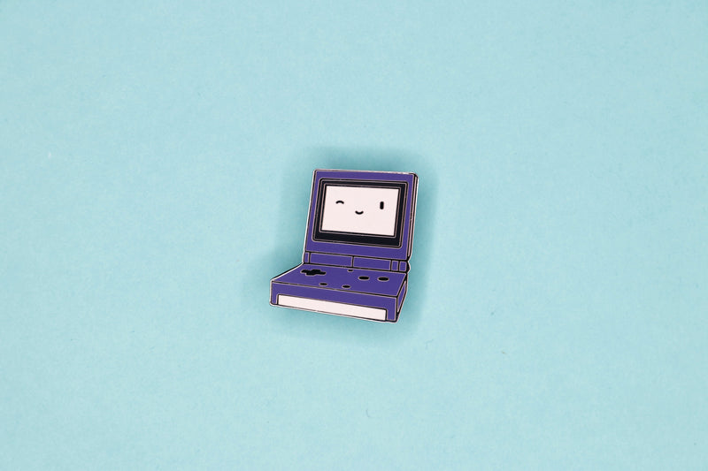 Purple Game Boy Advance SP Hard Enamel Pin on Teal Background