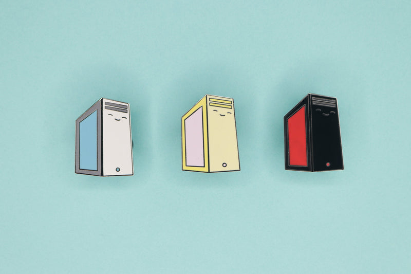 Gray, Yellow, and Black PC Tower Enamel Pins on Blue Background