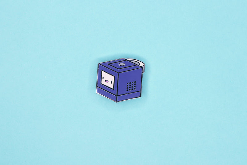 Indigo GameCube Hard Enamel Pin on Teal Background