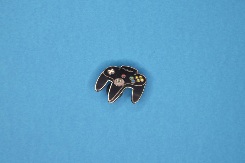 Charcoal N64 Controller Hard Enamel Pin on Blue Background