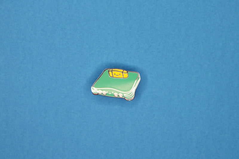 Jungle Green n64 with Donkey Kong 64 Game Cartridge as a Hard Enamel Pin on a Blue Paper Background