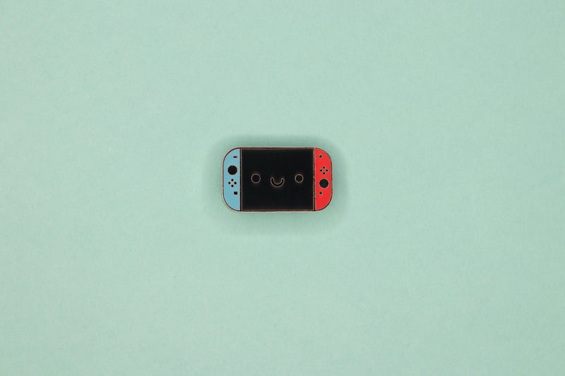 Neon Blue and Neon Red Switch Hard Enamel Pin on Teal Background