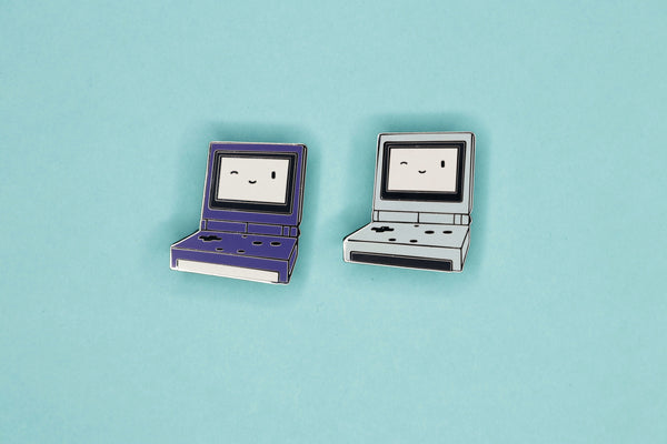Purple and Pearl Blue Game Boy SP Hard Enamel Pins on Teal Background