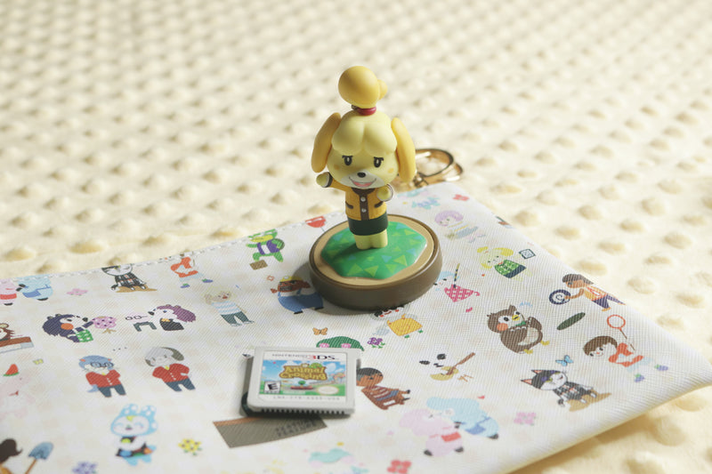 Isabelle Amiibo standing on Animal Crossing Pouch with Happy Home Academy Game Cartridge