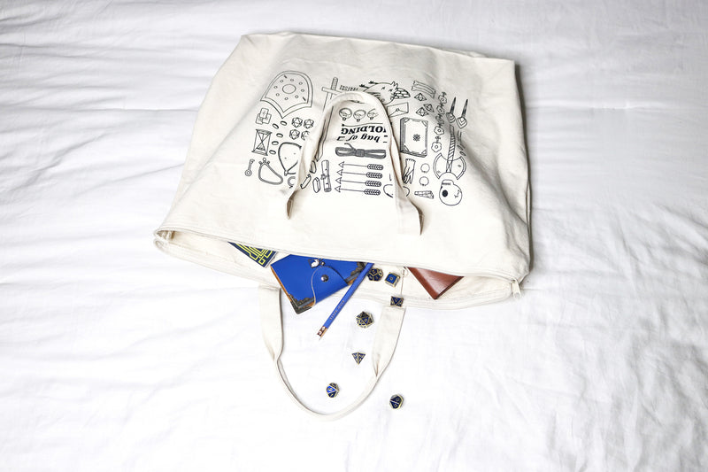 white bag of holding canvas tote bag with tabletop RPG supplies inside