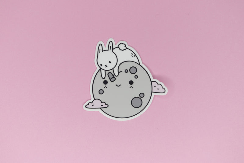 sticker of white bunny on grey moon with pink clouds