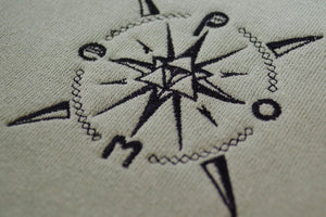 Closeup of pome compass logo on crewneck sweatshirt
