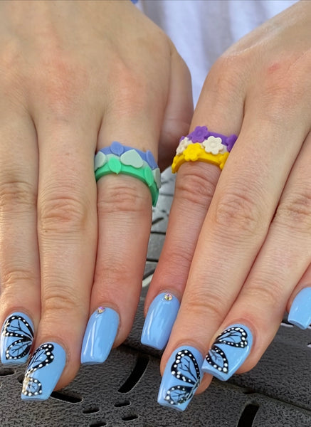 two hands wearing silicone ring bundles blue butterfly manicure