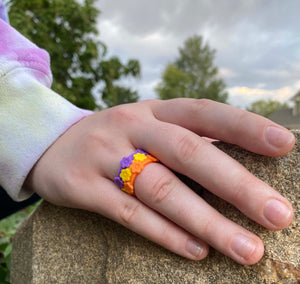 Hand Resting on Rock wearing Purple Yellow and Orange Flower Silicone Rings