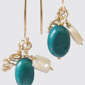Detail of turquoise earrings with nacar and wired leaf