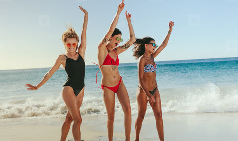3 women walking on the beach in swim suits
