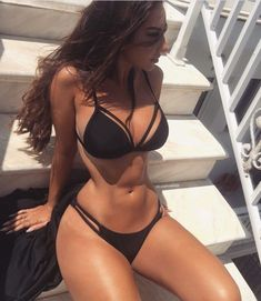 woman in black swimsuit sitting on stairs