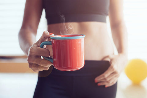 woman holding a red mug with Celebrity Detox Tea