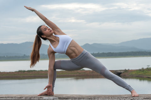 woman hold serious yoga pose near a body of water