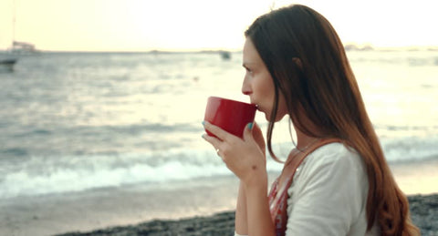 Woman drinking celebrity detox tea on the beach