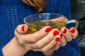 woman holding a hot cup of Celebrity Detox Tea in a clear tea mug with red finger nail polish
