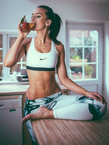 Beautiful young woman standing in kitchen with workout clothes drinking Celebrity Detox Tea