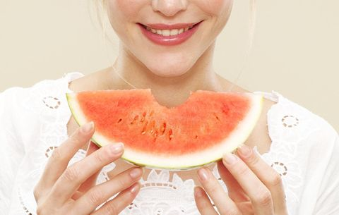 woman holding a slice of watermelon