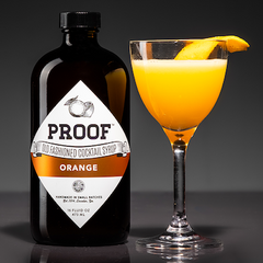 Orange Beach cocktail next to a bottle of Orange Proof Syrup