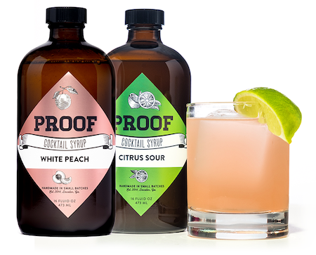 bottles of White Peach and Citrus Sour Proof Syrup next to a cocktail