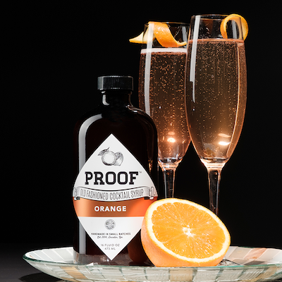 a bottle of Orange Proof Syrup on a silver tray next to half of an orange and two champagne cocktails
