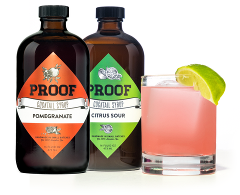 two bottles of Proof Syrup, next to a pomegranate margarita