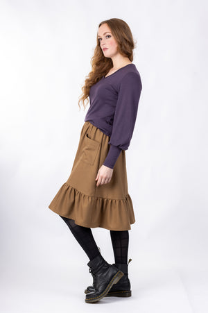 Forget-Me-Not Ella knee-length skirt pattern with pocket in brown, full-length side view of model