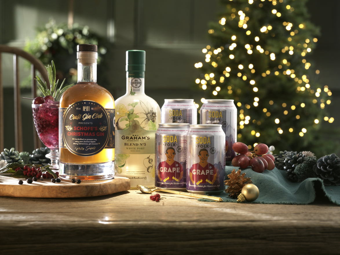 Gin and Port Bottles on a table with cans and festive decorations