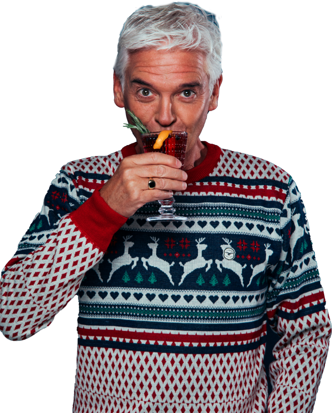Phillip Schofield sipping a Christmas cocktail in a festive jumper