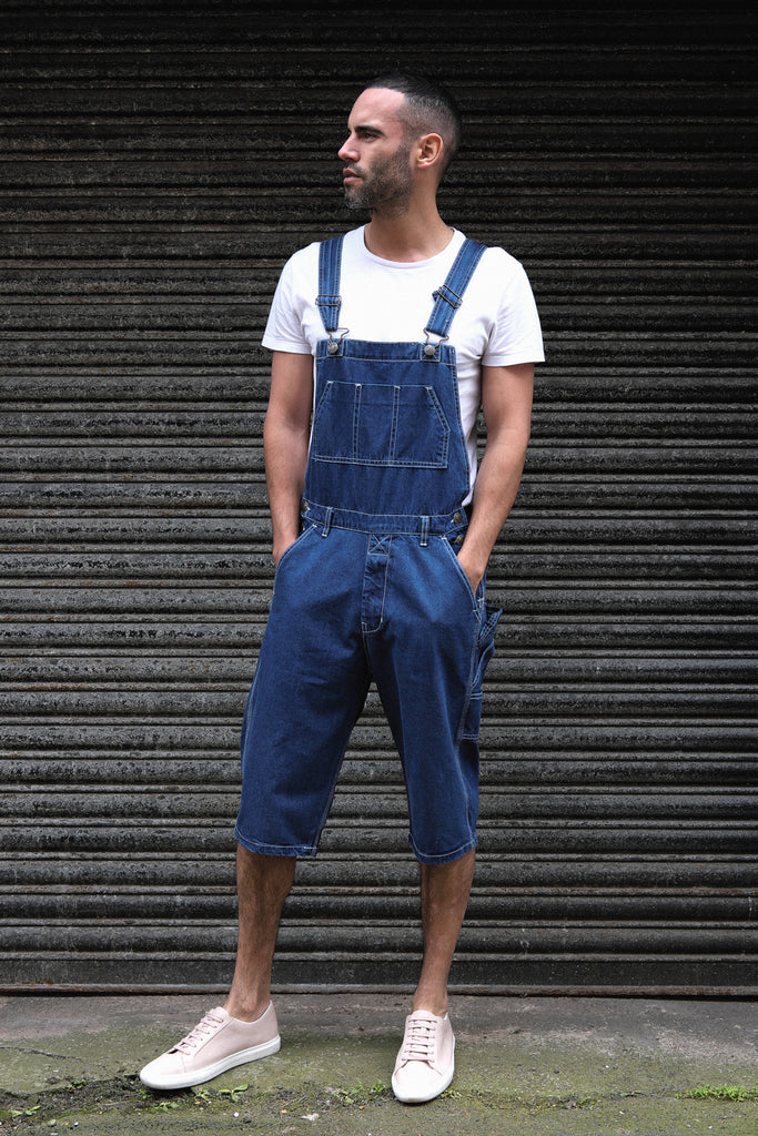 Skinny dungaree shorts paired with white t-shirt and trainers with grey shutters backdrop.