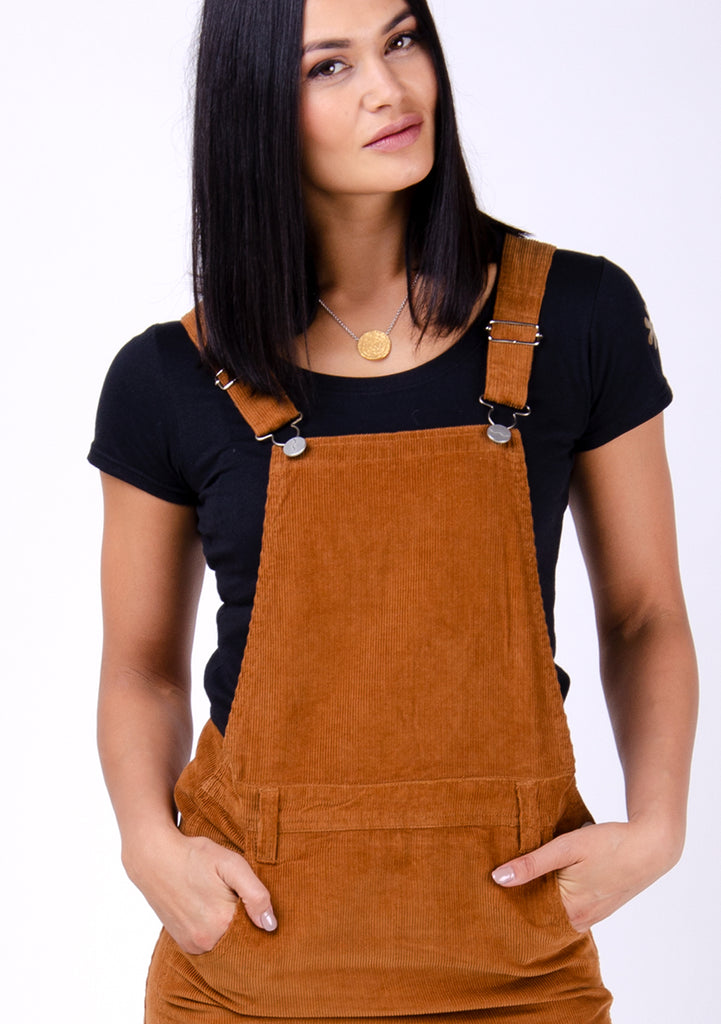 Brown autumnal corduroy dungarees with hands in front pockets, paired with black t-shirt.