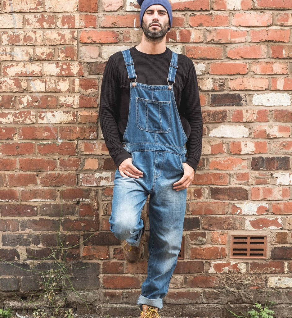 Man leaning against red brick wall wearing mid-wash denim dungarees styled with dark sweater and blue beenie hat.