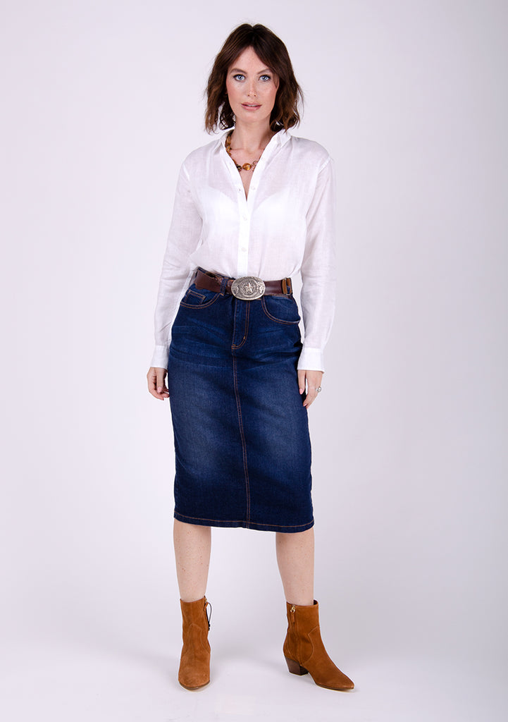 Close-fit dark blue denim midi-skirt styled with tan suede boots, white blouse and chunky belt.