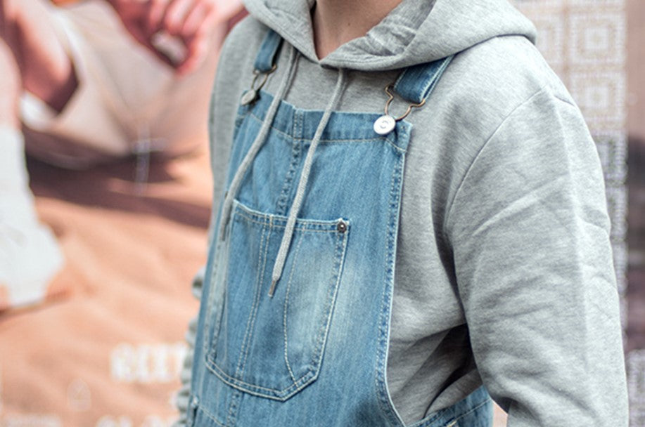 Focus on bib area of mid-wash dungarees paired with grey hoodie.