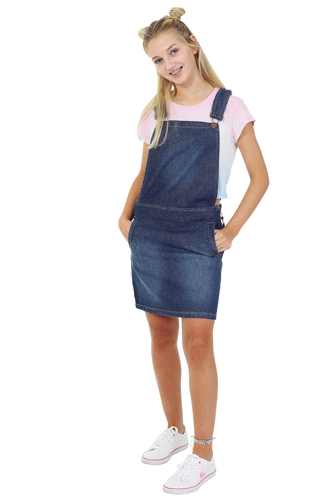 Wearing denim bib overall dress and 2-tone t-shirt with hands in pockets.