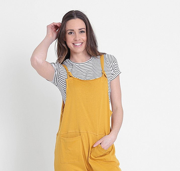 Oversized yellow dungaree jumpsuit, paired with striped t-shirt and hand in left pocket.