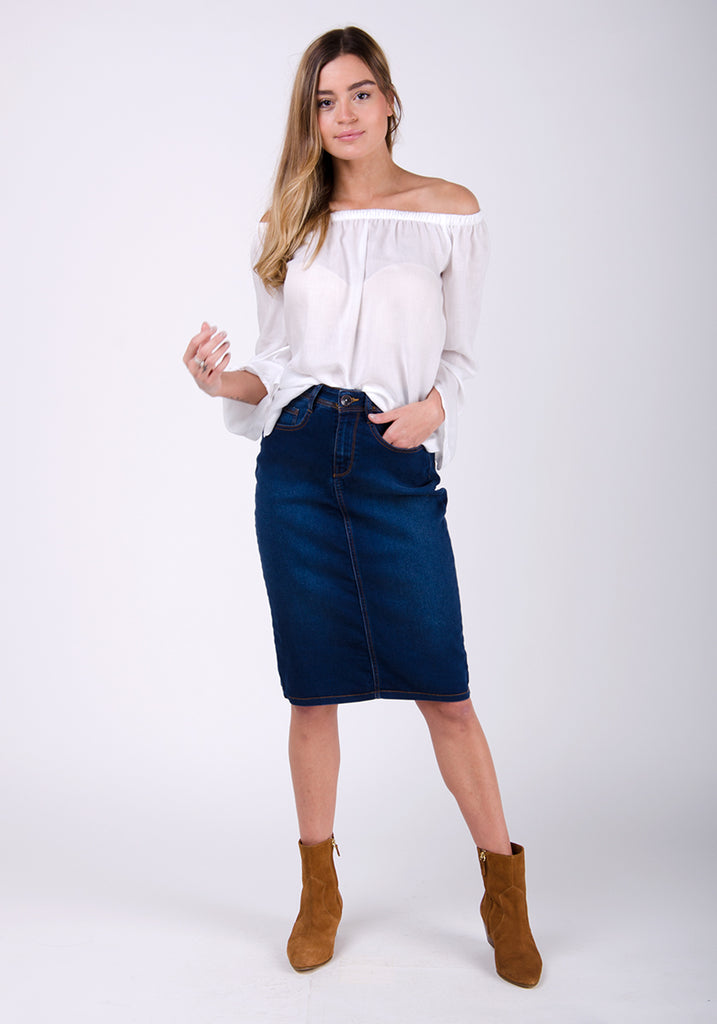 Close-fit dark blue denim midi-skirt styled with tan suede boots and white blouse.