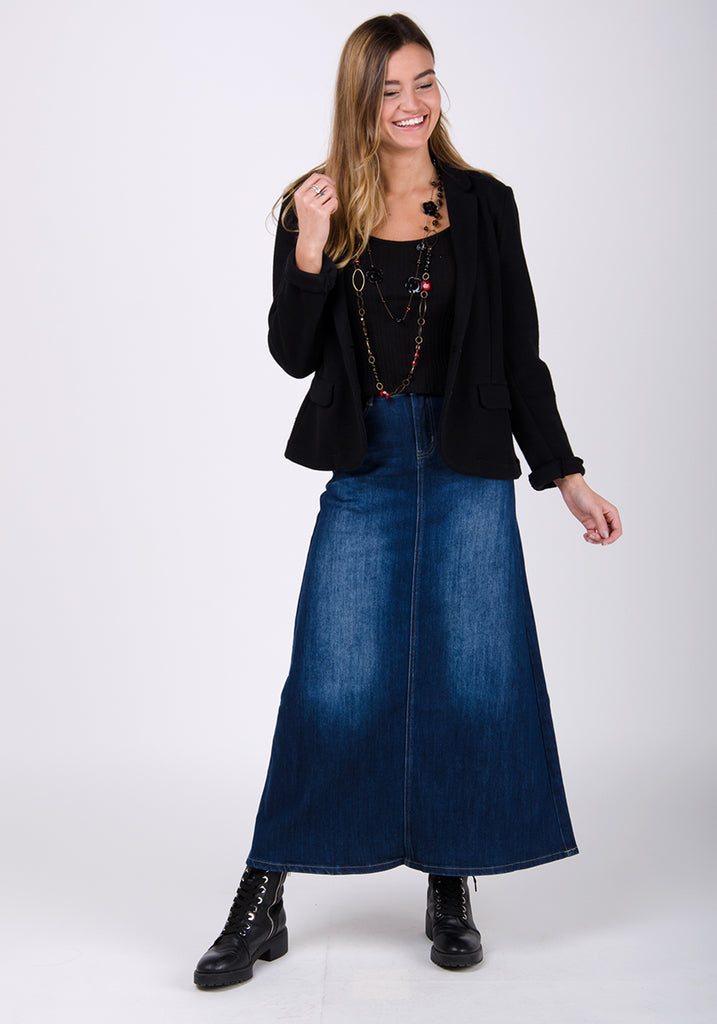 Ankle-length dark wash denim skirt styled with black boots and blazer.