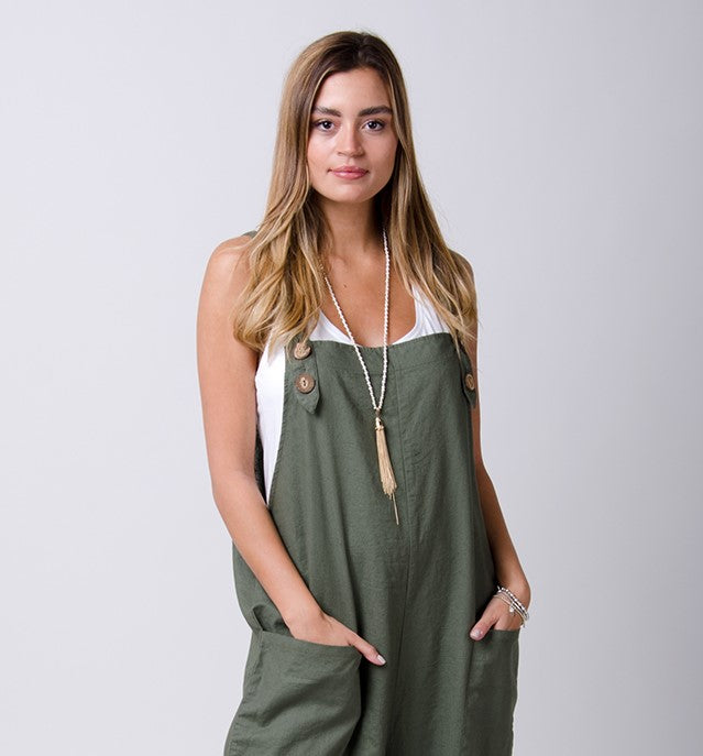 Green maternity dungarees with hands in pockets.