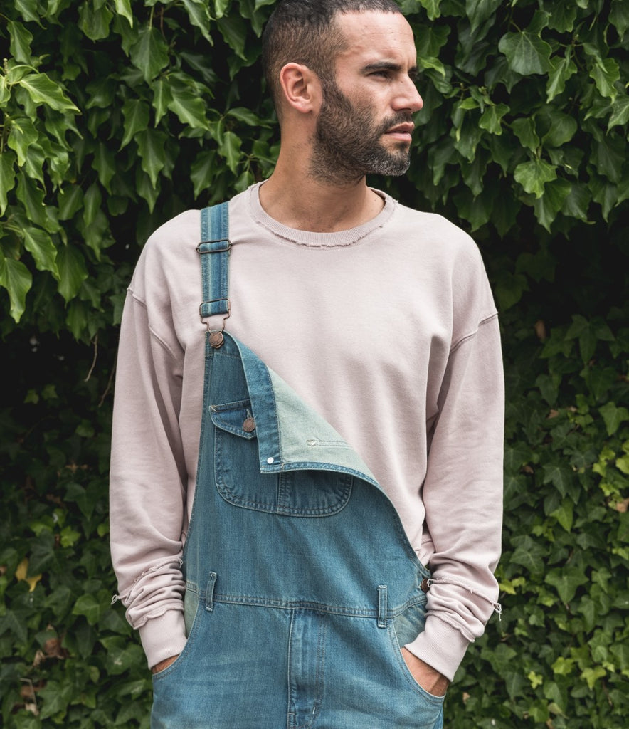 Men's pale wash denim bib overalls with one bib strap unsecured to reveal back of bib fabric and pale pink sweater.