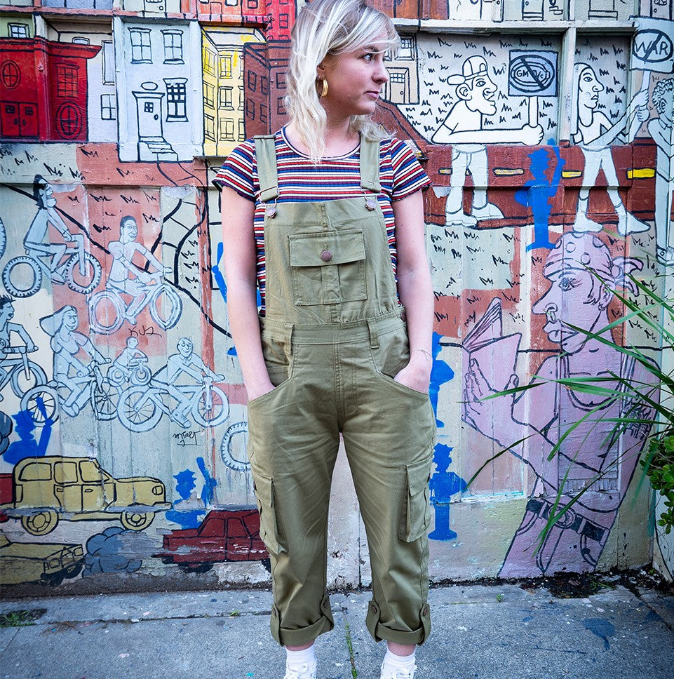 Wearing olive dungarees with hands in front pockets against colourful graffiti backdrop.