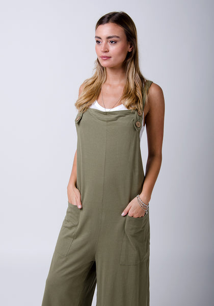 Olive, loose fit jumpsuit with hands in front pockets.