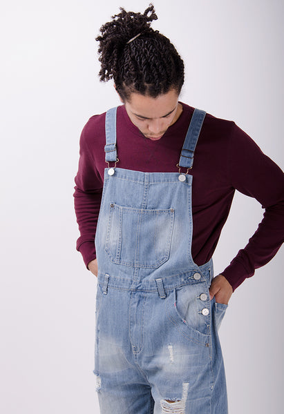 Front shot of men's pale wash denim overalls with abrasions.